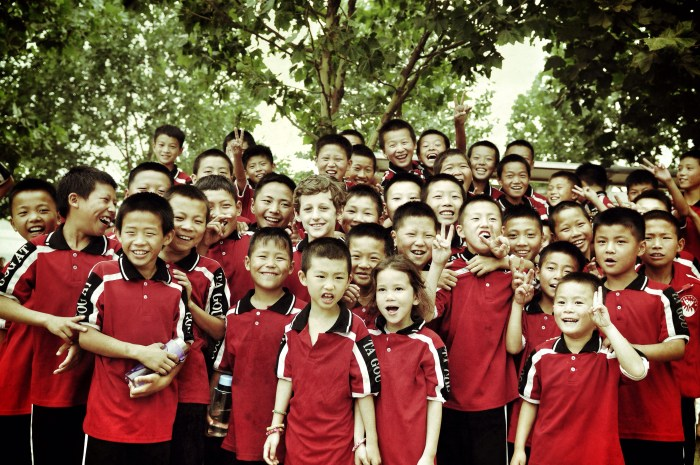 A large group of children, Chinese and Caucasian, wearing the uniform of the monastery, pose smiling for the camera.