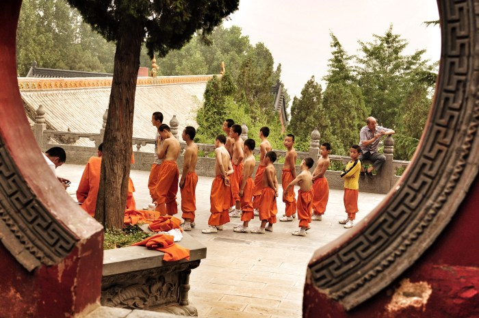 A group of boys from young to teenager wearing orange trousers prepares for a lesson