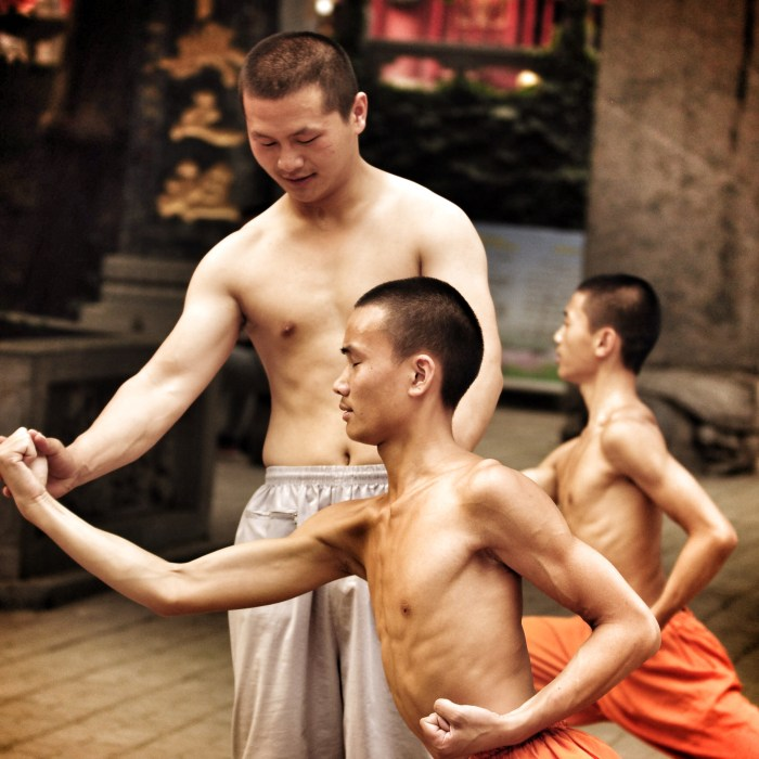 An instructor adjusts the stance of a young man practicing a wushu form, eyes closed.