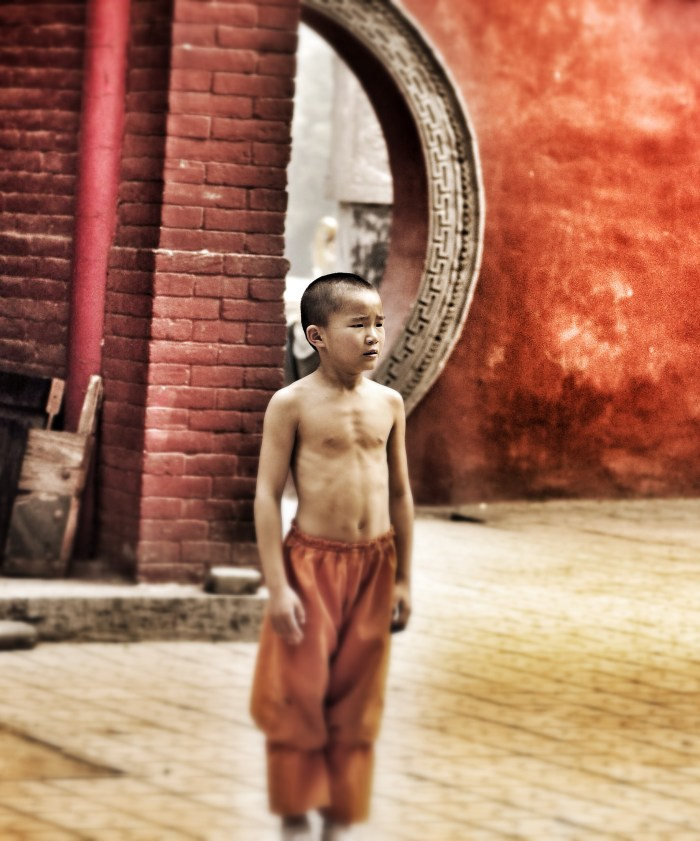 A young boy stands in front of a Chinese key-shaped door wearing the orange pants of a Shaolin warrior.