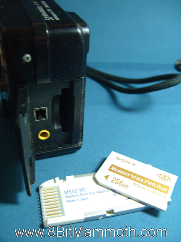 A photo showing part of a camera, a memory card and adapter.