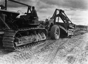 Black soldier operating D8 dozer and carryall along Alaska Highway.