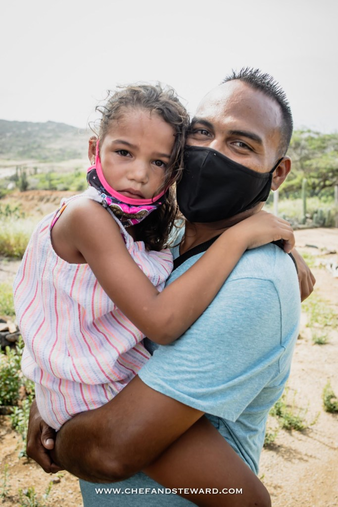 Masked Aruban father holds daughter with face mask off at Aruba Ostrich Farm Tour for what to do in Aruba