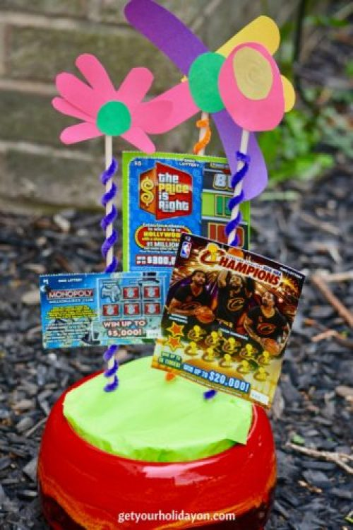 Diy flower pot that has lottery tickets and flowers sticking out to make a scratch off bouquet.