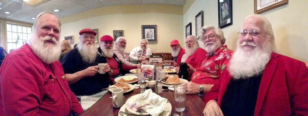 Great group of Santa Clauses, one elf and one helper enjoy a little breakfast and a nice chat.