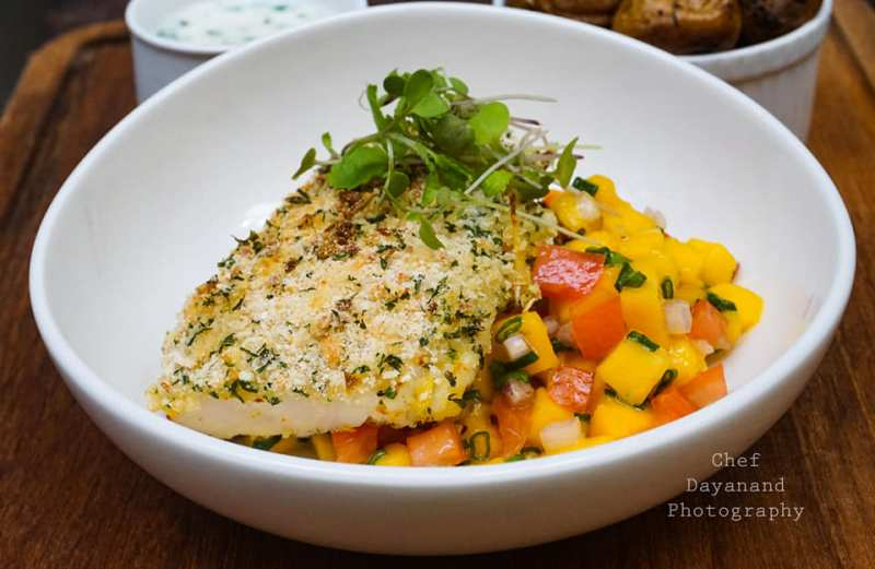 BAKED FISH WITH GREMOLATA CRUMBS, FRESH MANGO SALSA & HERB ROASTED POTATOES SERVED WITH CHIVE CREAM SAUCE.