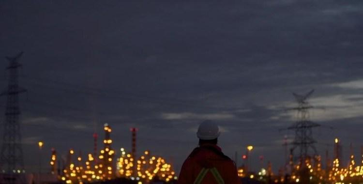 oil refinery lights man standing