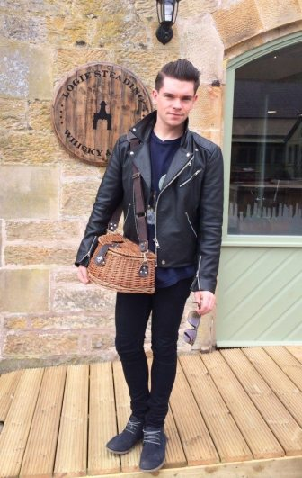 Robin James outside Logie Steading Whisky & Wine Shop with fly fishing basket