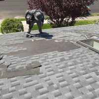 a man repairing and replacing roof shingles
