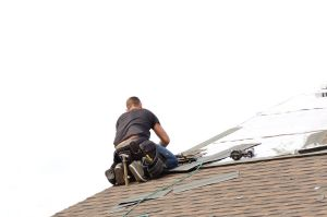Roofer laying down asphalt roof shingles at a large commercial housing