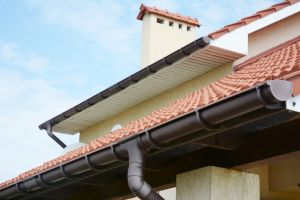 Rain gutters system on new house with chimney, red clay tiled roof