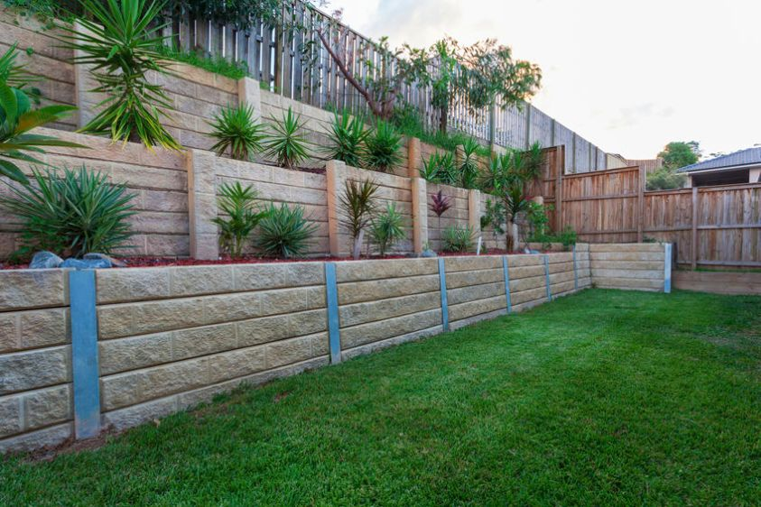 Multi level retaining wall with plants in backyard