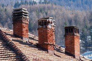 three old damaged chimneys made of bricks