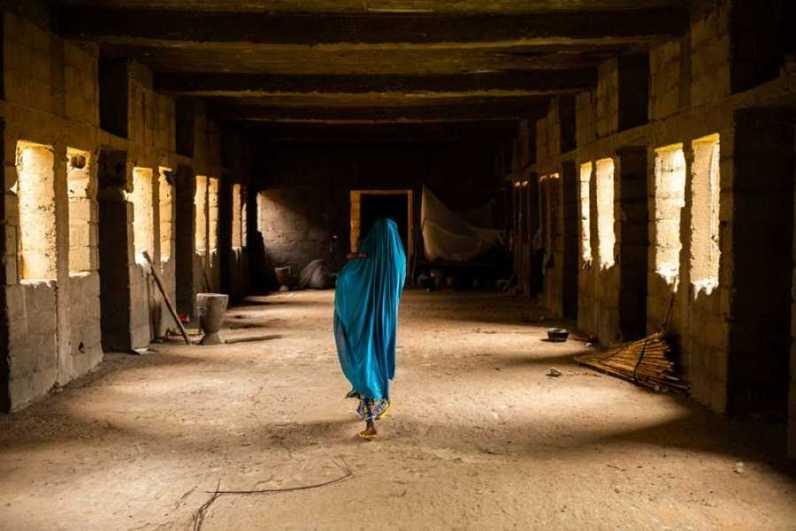 Aisha A., de 50 años, lleva cuatro viviendo en el pasillo a cielo abierto de uno de los edificios en ruinas de Anka. Ha tratado de cerrar algunas de las ventanas con barro para protegerse de las inclemencias del tiempo. Benedicte Kurzen/NOOR Benedicte Kurzen