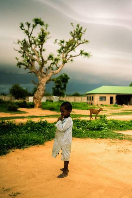 """Muhammad (nombre ficticio), de 3 años de edad, de pie, cabizbajo, en el campo de desplazados conocido como """"Nuevo palacio del Emir"""". Benedicte Kurzen/NOOR Benedicte Kurzen"""