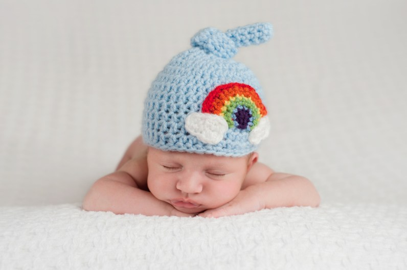 A sleeping, three week old, newborn baby boy wearing a top knot beanie with rainbow design. Shot in the studio on a white blanket.