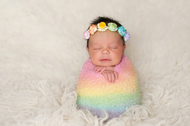 A sleeping nine day old newborn baby girl bundled up in a rainbow colored swaddle. She is propped up on a cream colored flokati (sheepskin) rug and wearing a crown made of roses.