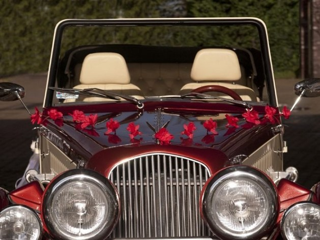 Red coloured car decorated with red flowers and pink ribbon.