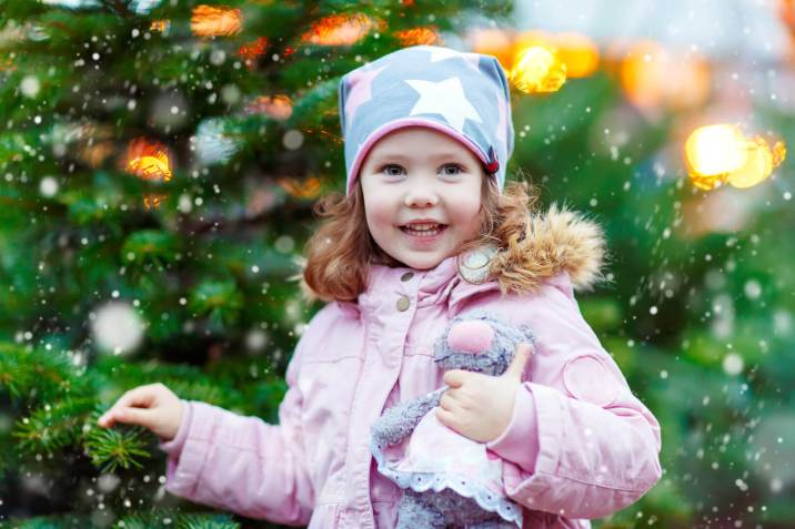 picture of a little girl holding a Christmas tree (or xmas tree)