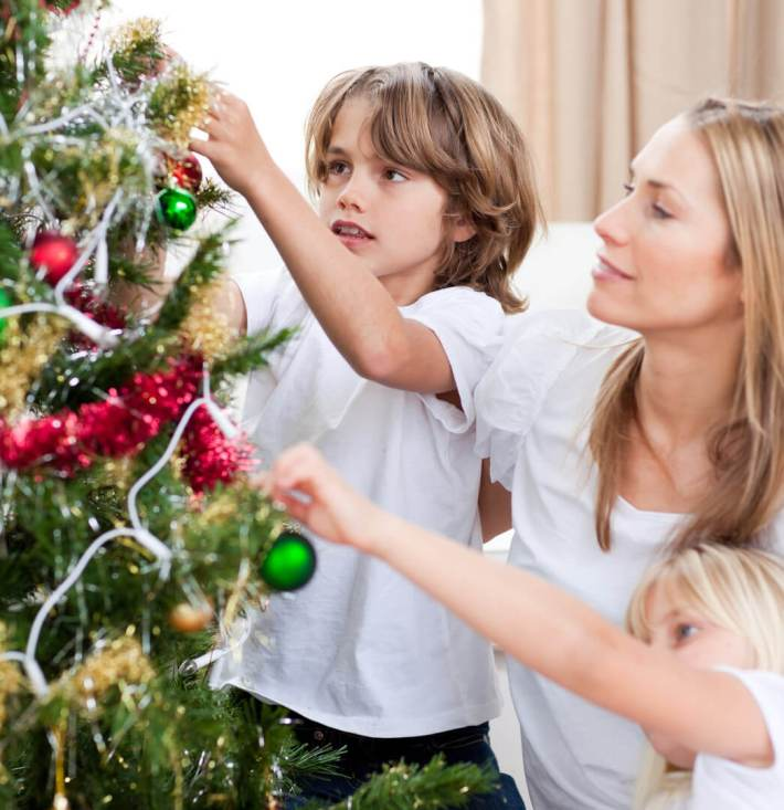 picture of a family decorating a Christmas tree (or xmas tree)