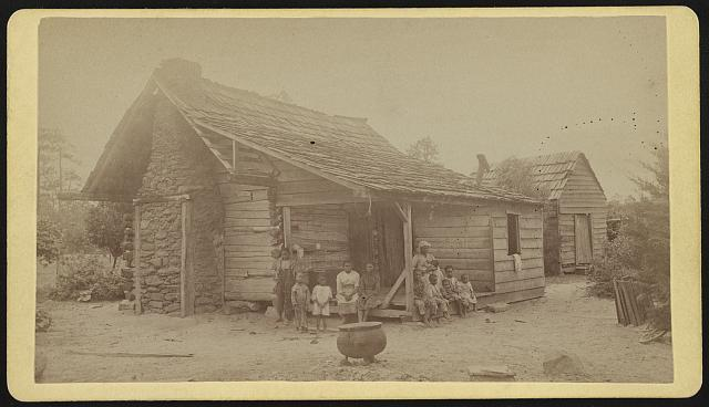 A large African American family of mostly women and children, gathered around the porch of a log and clapboard cabin, with wood shingle roof and stone chimney, and a large cauldron in the foreground, and with a small shed in the background.