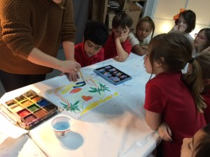 A teacher shows several students how to paint a landscape painting.