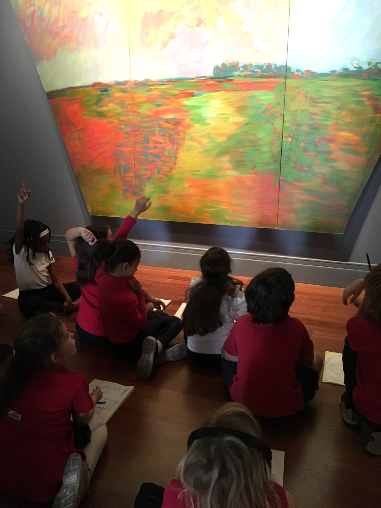 Several students sit cross-legged looking at a painting on the wall.