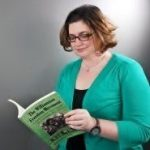 Woman standing in a green sweater reading a textbook wearing glasses with ear length brown hair