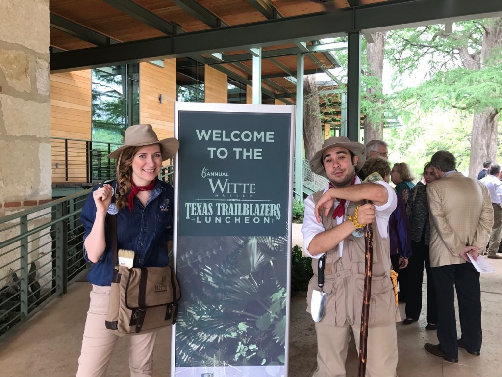 A female and a male staff member pose alongside a sign for Texas Trailblazers
