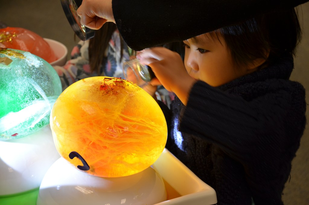 Young child examining a glowing orb closely