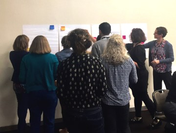 Group of people with their backs to the camera adding comments to several flipchart pages stuck to a wall
