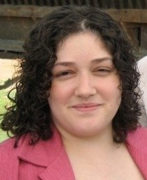 Image of woman with curly short dark colored hair smiling at the camera