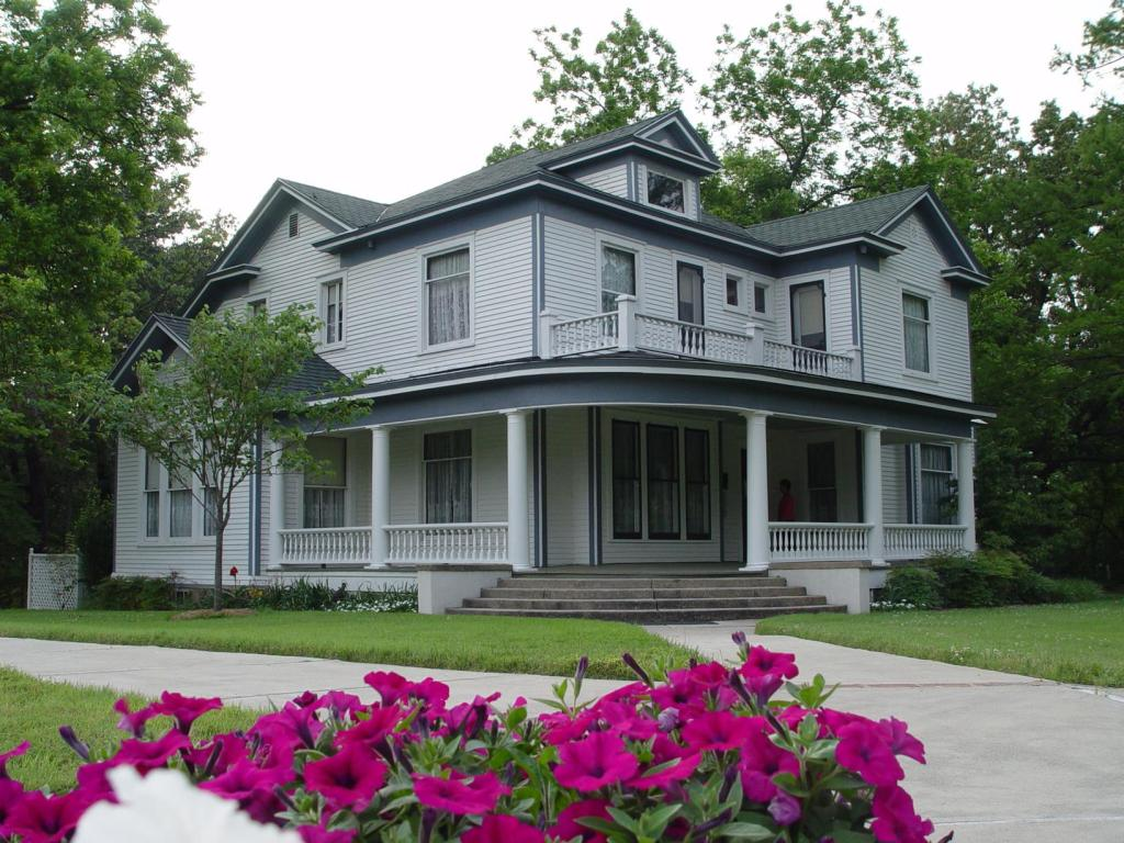 Exterior image of the front of the historic house two stories painted gray with a wrap around porch