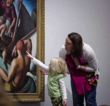 A young child points at part of a person in the painting while an adult stoops intently toward them.