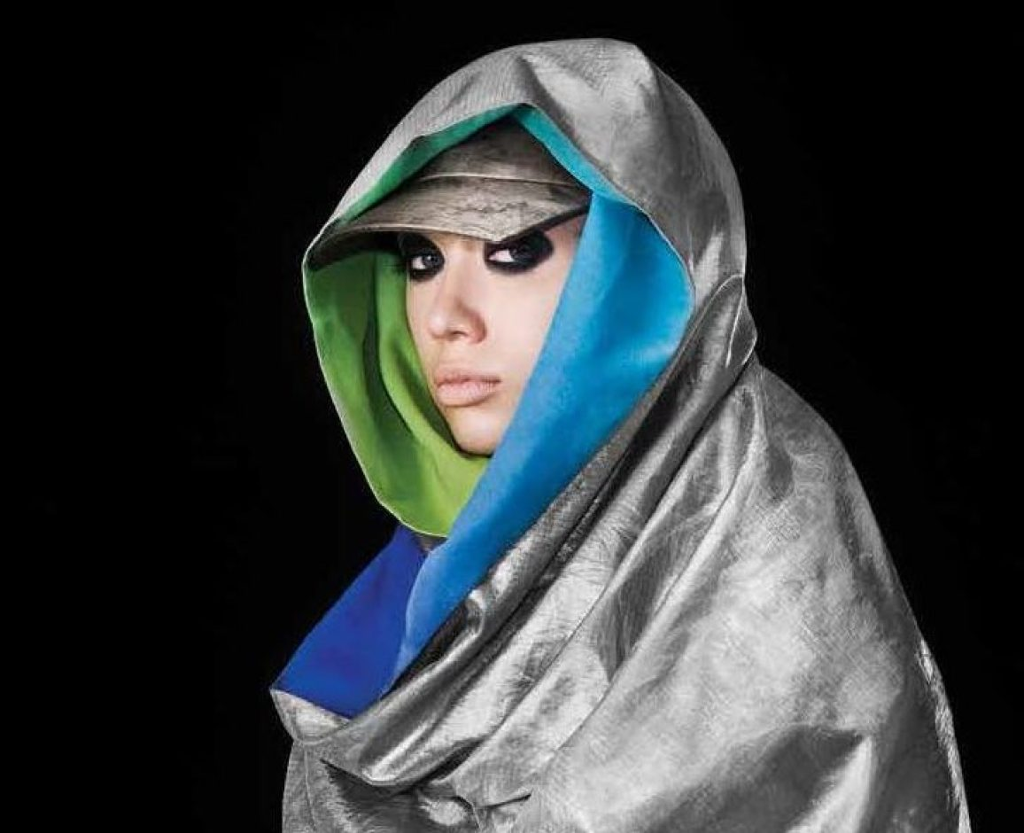 A woman wearing a metallic fabric scarf on her head and shoulders looks into the camera