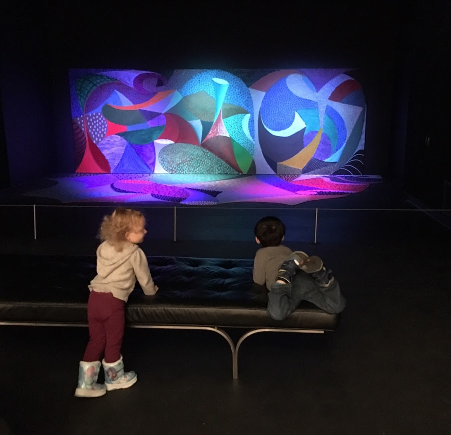 Two children play on a bench in front of a colorful piece of artwork.