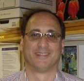 A man stands smiling at the camera wearing glasses and a striped shirt.