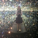 A woman stands in a Kusama installation and takes a selfie.