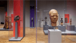 Image of a museum gallery with grey plinths containg objects the closest object is a carved wooden head, possibly African.