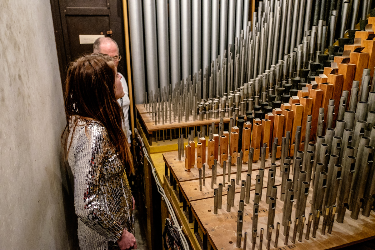 A woman in a sparkly shirt stands next to a set of pipes listening to a guide discuss how the pipe organ is used.