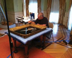 A man works on removing dust from a painting of George Washington. The painting is placed on a blanketed table.