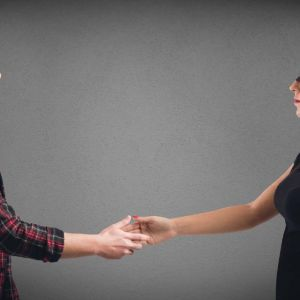 A blindfolded man and woman reach to shake hands with each other. This represents an unbiased hiring process.