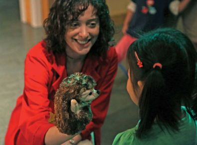 A woman is showing a child a hedgehog puppet.