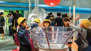 A group of children stand around an air conduit wearing hard hats.