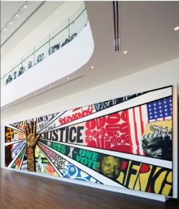 Image of a mural hanging on a wall with a giant raised hand and words and images radiating out from it.