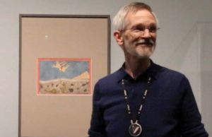 Jeff Byers standing in front of a framed sketch on paper.