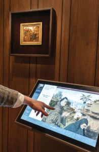 Image of someone's arm pointing at an angled interactive screen with a drawing of two figures on it.