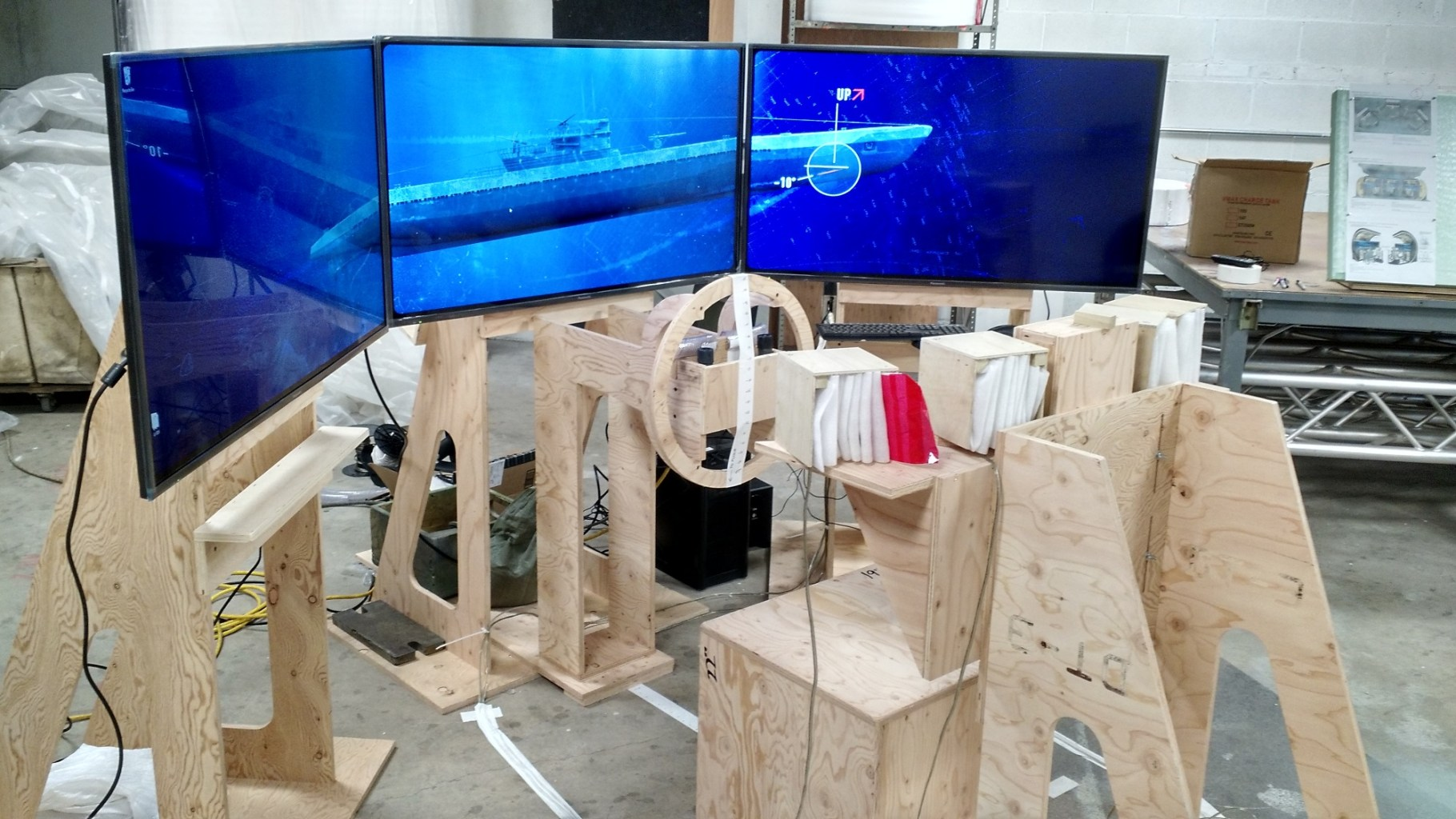 An image of three LCD screens in a semi circle standing on saw horses in a workshop with the image of a submarine displayed on the screens.