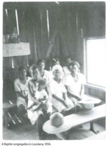 Black and white image of several African American women sitting on benches in a wooden structure.
