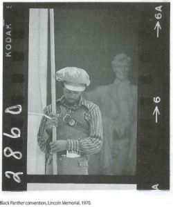 Image of a black and white photo negative of an African American man standing outside the Lincoln memorial holding a long pole.